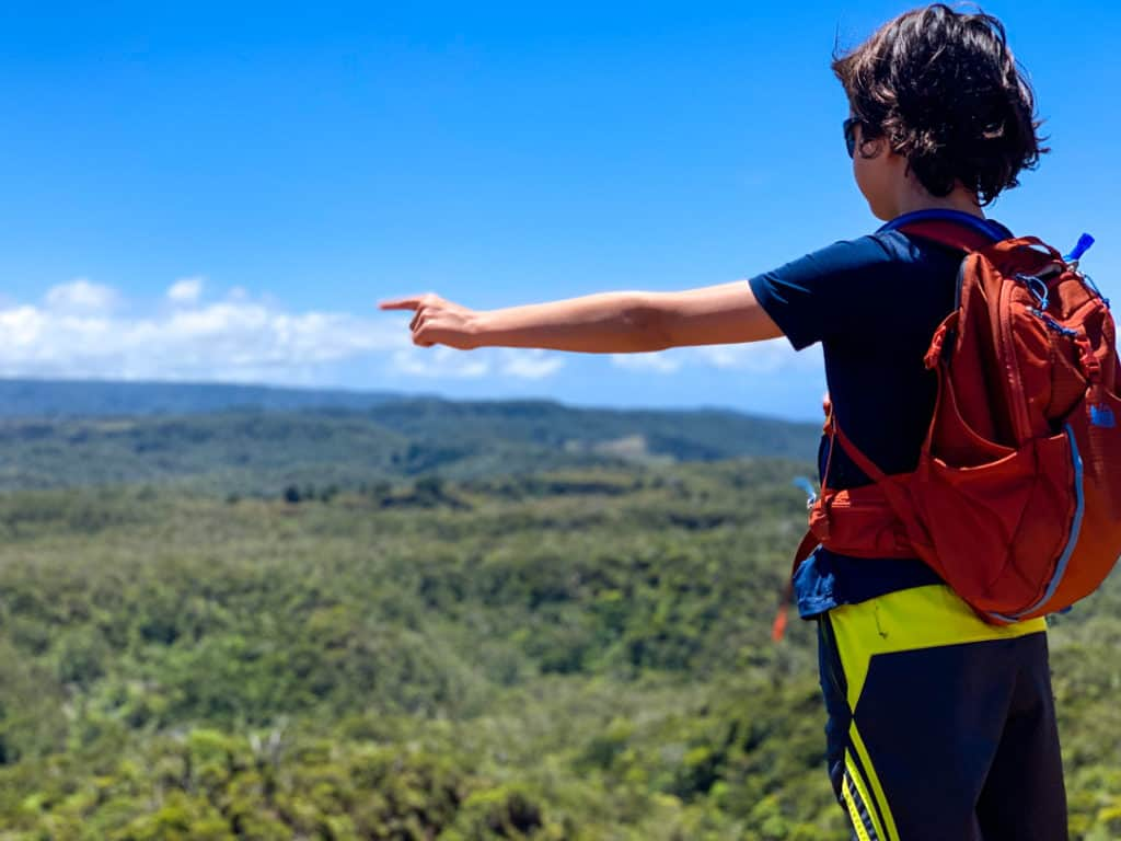 Boy wearing sunglasses and backpack pointing into Waimea Valley