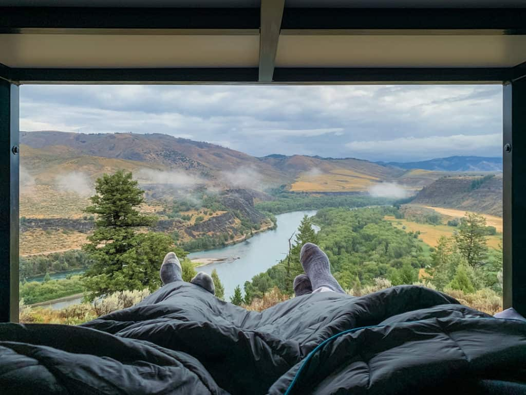 view of snake river out back of campervan with two pairs of feet crossed and sticking out under grey blanket while camping overnight