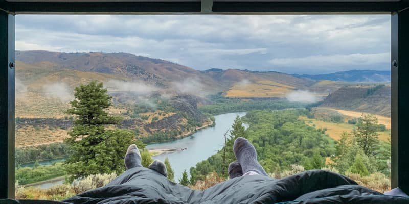 view of snake river out back of campervan with two pairs of feet crossed and sticking out under grey blanket