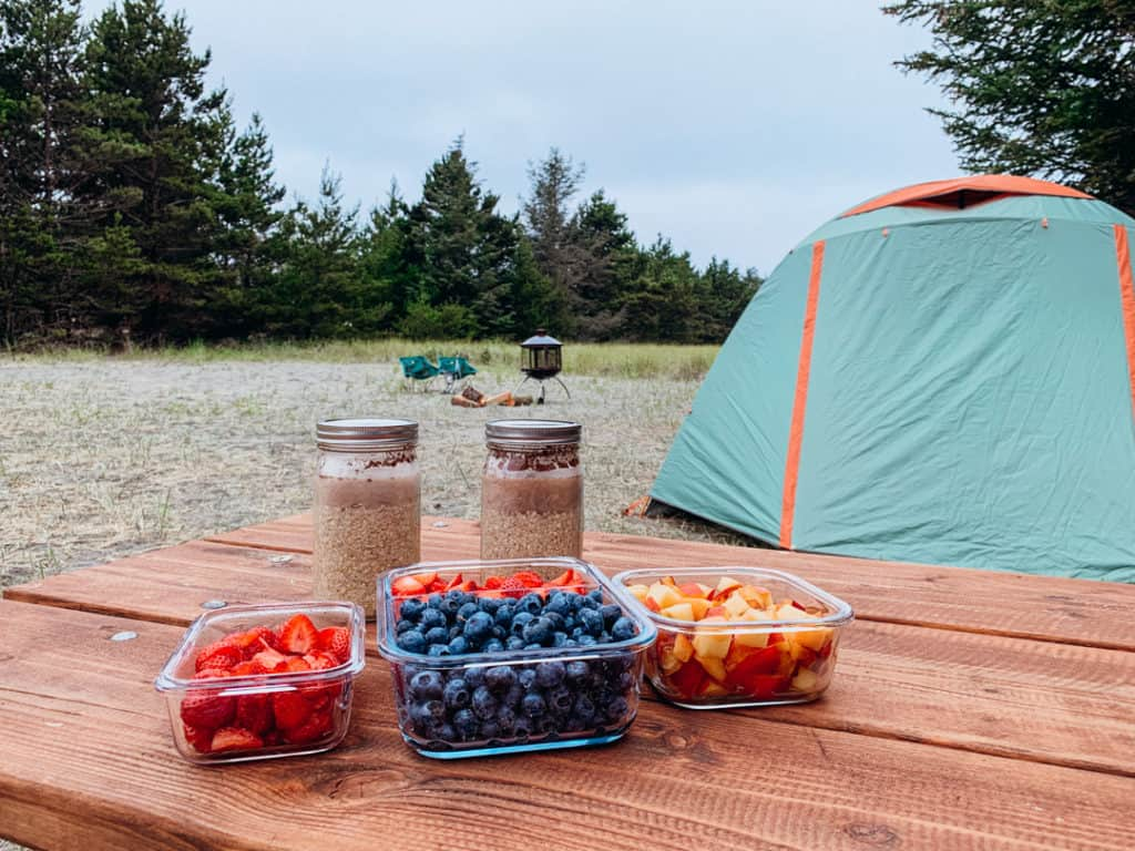 camping image with picnic table in foreground with two mason jars of overnight oats and 3 containers of fresh fruit on top with tent, fire pit and camp chairs in the background