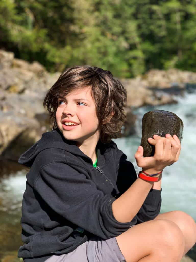 boy holding large rock, smiling, and looking back over his right shoulder