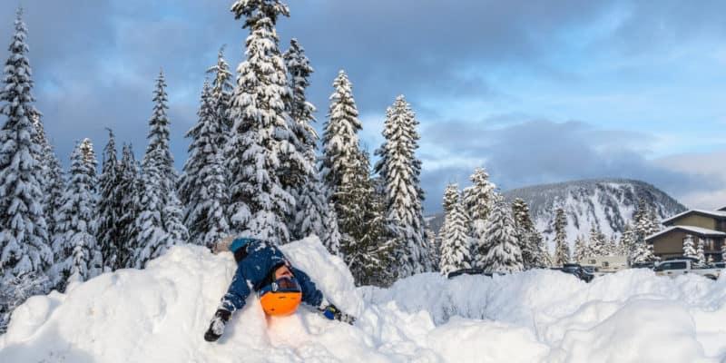 boy laying upside down on snow pile in blue coat and orange helmet