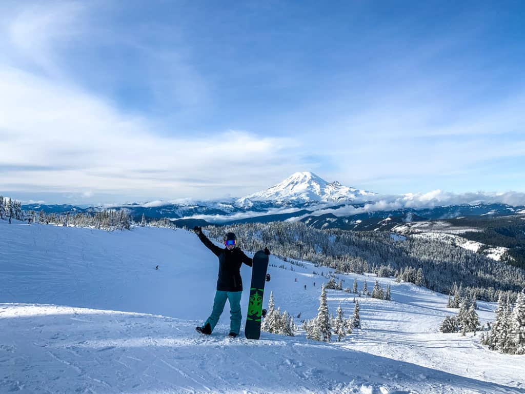 woman standing on snowy ridge in front of Mt. Rainier holding up a snowboard