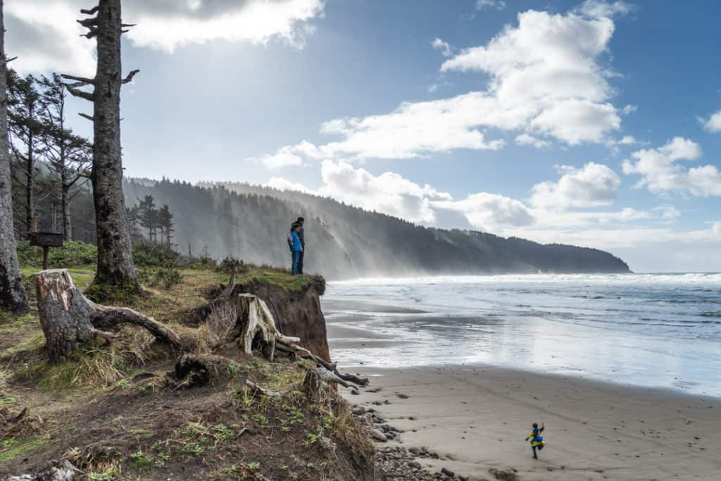 father and son standing on ledge over beach while boy runs on sand below them near campground at Cape Lookout State Park in Oregon