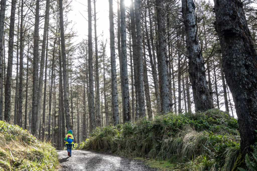 boy hiking on forested trail with bright tie dye sweatshirt near the campground at Cape Lookout State Park