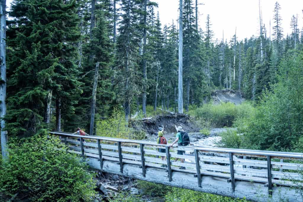 father and two sons crossing wooden bridge carrying backpacks with the things to bring on a hike