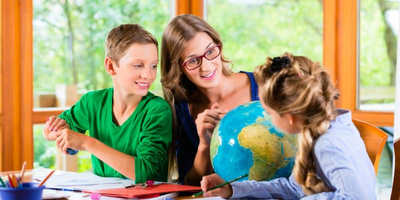 mother teaching two children geography lesson during homeschool