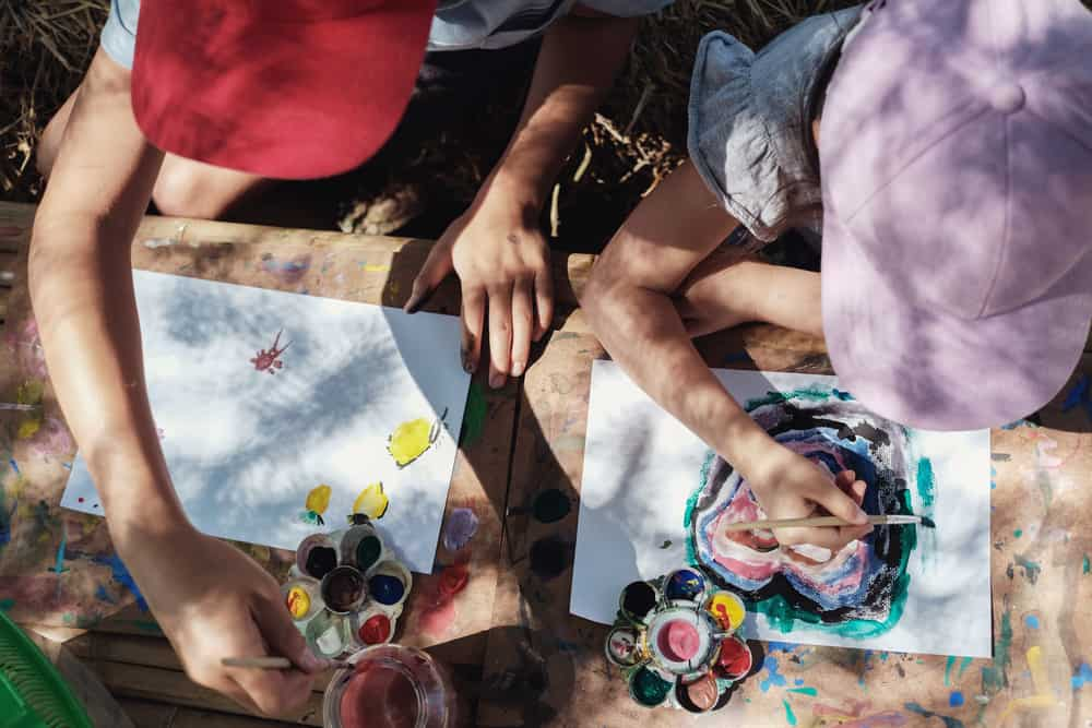 Kids painting outdoors during homeschool art lesson