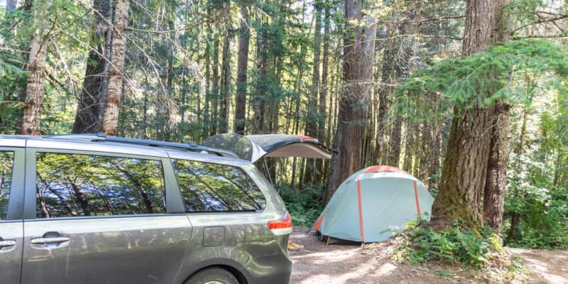 grey sienna with back open and tent set up in background in the trees