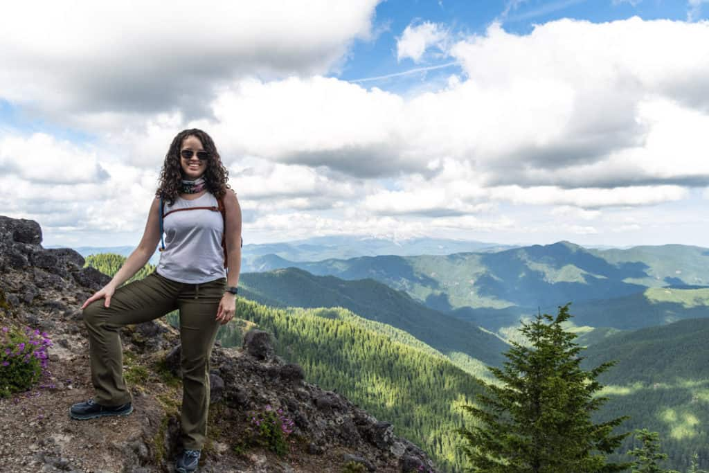 woman at top of hike with incredible view and clouds in a bright blue sky